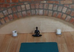 Yoga mat with two candles and statue