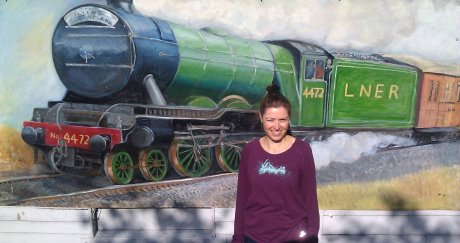 Person in front of train mural.
