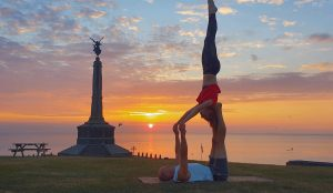 Two people balancing on each other with sunset in background