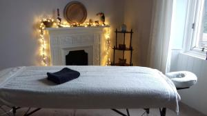 Room with massage table and fireplace with lights behind