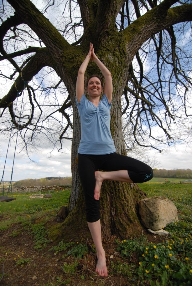 Alyson standing in tree pose infront of a tree