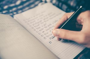 Notepad with list and person's hand, writing the list