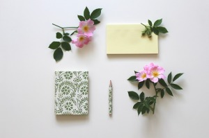 Notepads and flowers on table