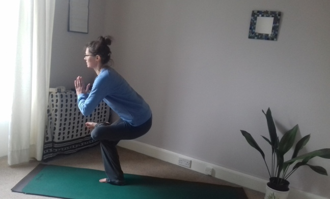Female in standing yoga pose with one leg crossed over the other